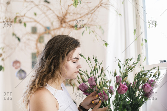 Boho teenager smelling fresh flowers isolate at home