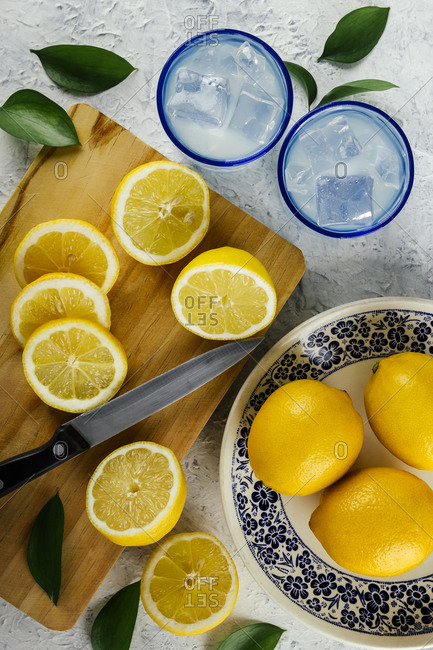 Freshly cut lemons with glasses of lemon juice at an outdoor picnic