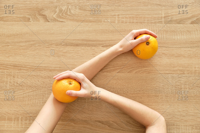 Juicy tomato in hands on wooden background