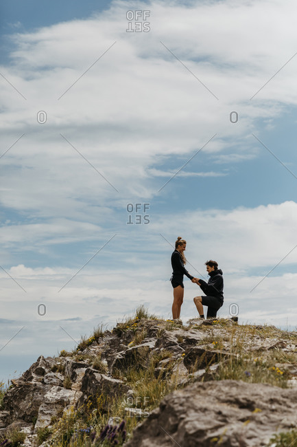 Happy boyfriend puts a ring on his girlfriend's hand after proposal