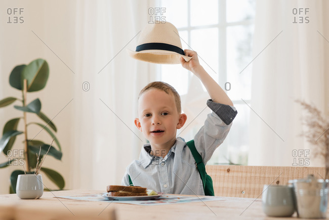 Boy holding his hat up whilst eating his lunch at home smiling