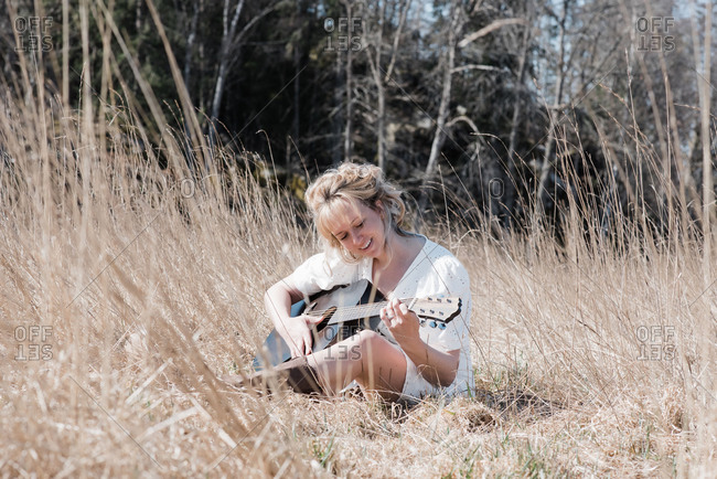 Woman sat in a field happily playing guitar in summer