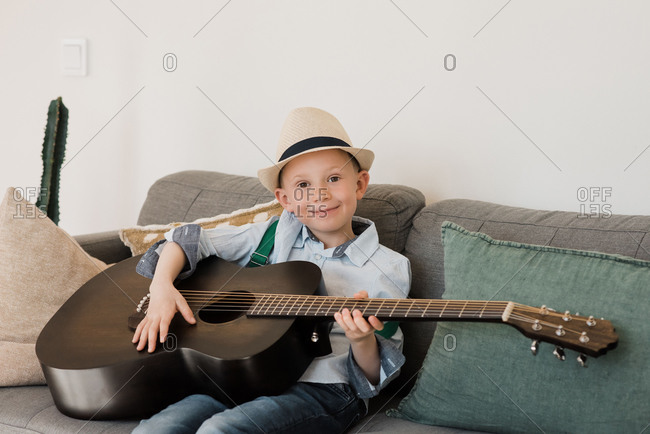 Boy smiling whilst playing guitar with a hat on at home