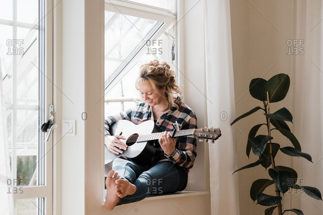 Woman sat at home on a window ledge smiling playing guitar