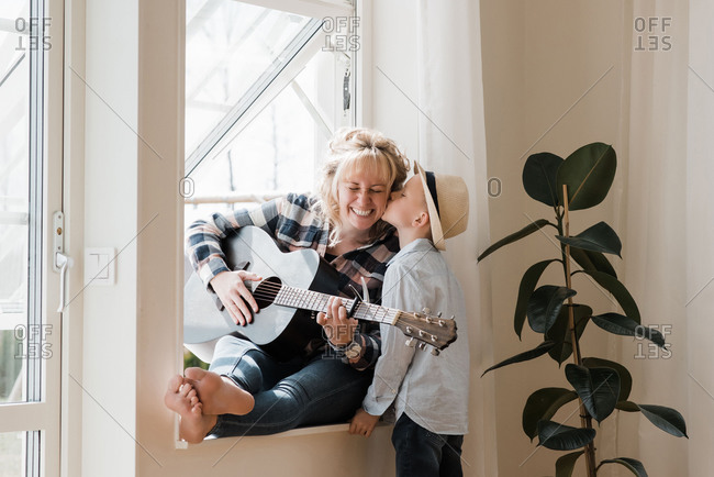 Woman sat playing guitar at home whilst her son gives her a kiss