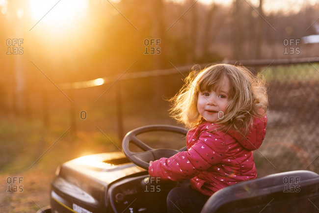 A two year old toddler girl pretending to drive a lawn mower.