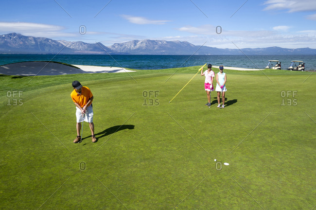 Three people playing golf at Edgewood Tahoe in Stateline, Nevada.