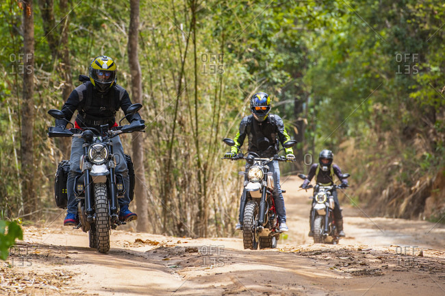 Three friends riding their scrambler motorcycles through forest