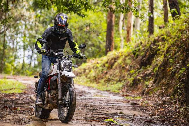 Man riding his scrambler type motorcycle through forest