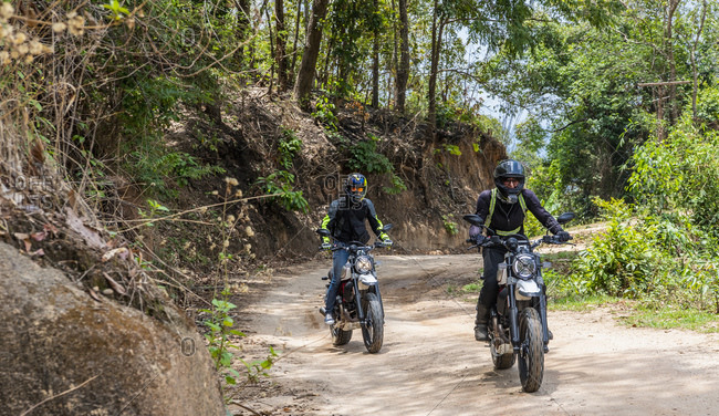 Two friends riding their scrambler motorcycles through forest