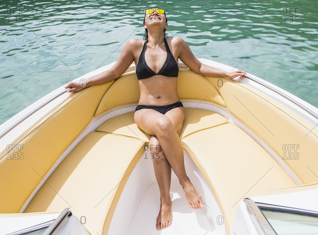 Woman sunbathing at the bow of a motor boat at a tropical island