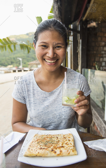 Woman enjoying a drink and a snack at the tropical Island Ilha Grande