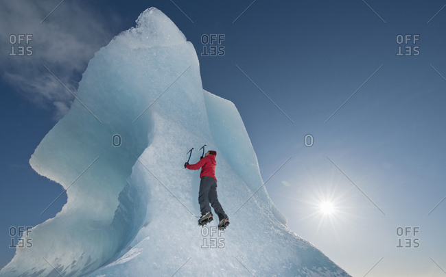 Woman climbing iceberg on the Fjallsjoull glacier lagoon