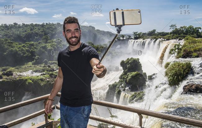 Man taking a selfie with monopod at Iguazu waterfalls in Argentina