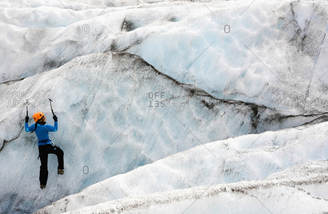 Woman climbing ice wall on Solheimajokull glacier in Iceland