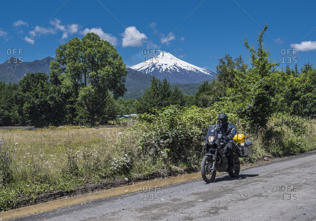 Motorbike rider passing the strato volcano Villarica, Chile