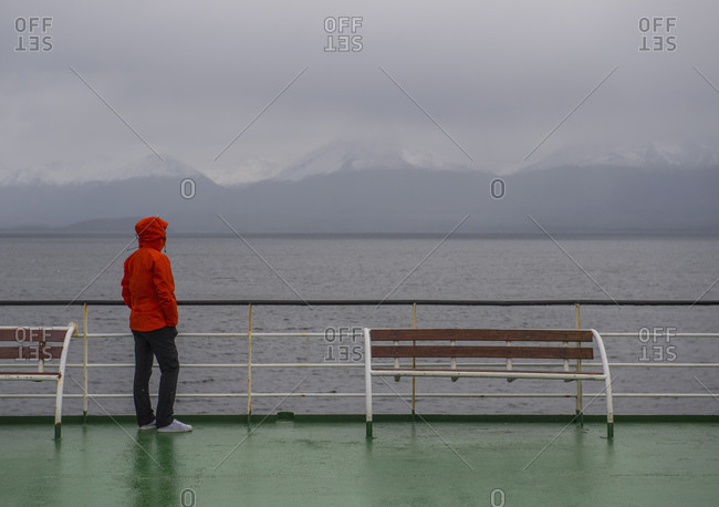 Woman looking at grim scenery from passenger vessel in Patagonia