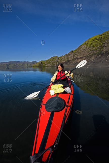 Woman rowing sea kayak on still lake in central Iceland
