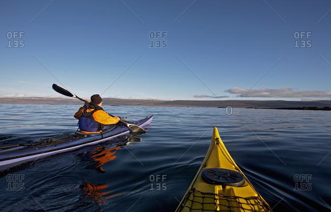 Two sea kayaks navigating through still lake on the Icelandic highland