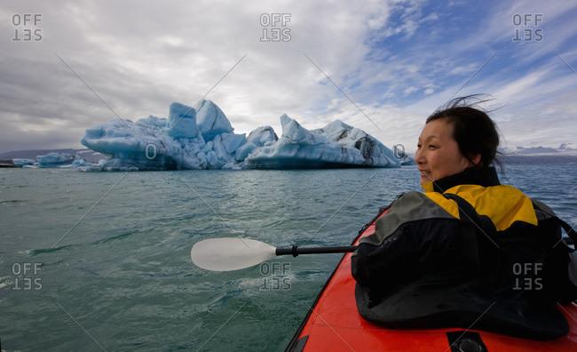 Woman rowing sea kayak on Jokulsarlon glacier lagoon in Iceland