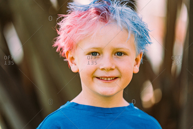 Young boy with colored hair smiling at camera