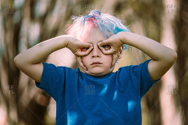 Young boy making upside down hand glasses