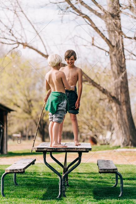 Two boys playing on picnic table