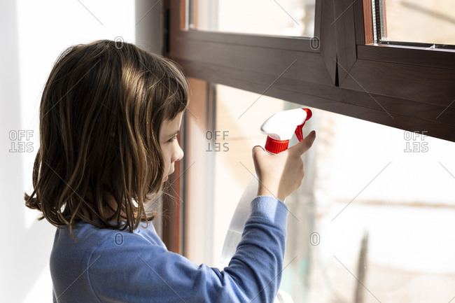 Girl helping at home to clean the windows during the coronavirus quarantine
