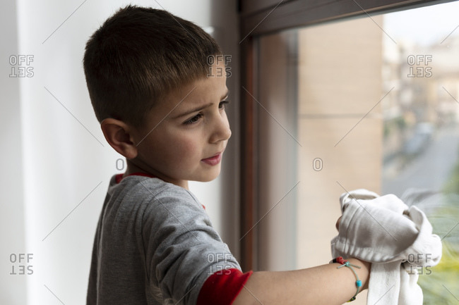 Boy helping at home to clean the windows during the coronavirus quarantine