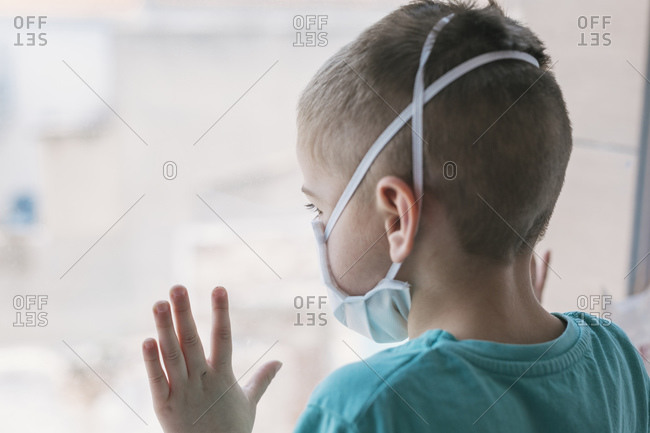 A small child in a medical mask is quarantined at home due to the spread of coronavirus infection. Child in medical mask looking through window