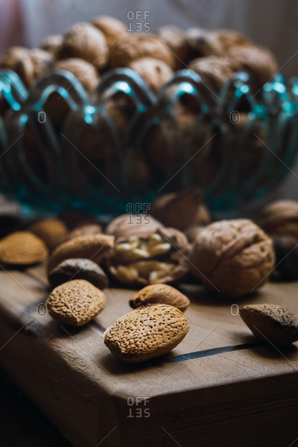 Walnuts and almonds in a blue glass bowl on a rustic wooden table