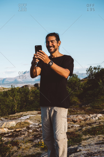 Man smiling taking a photo with his smartphone on top of a mountain