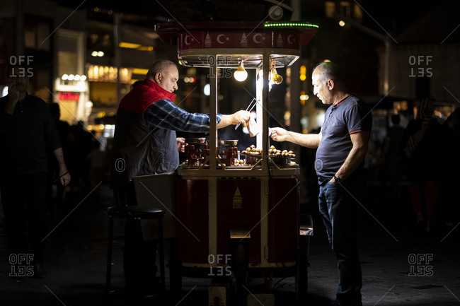 Istanbul, Turkey - September 3, 2019: Man buying chestnuts in Taksim Square