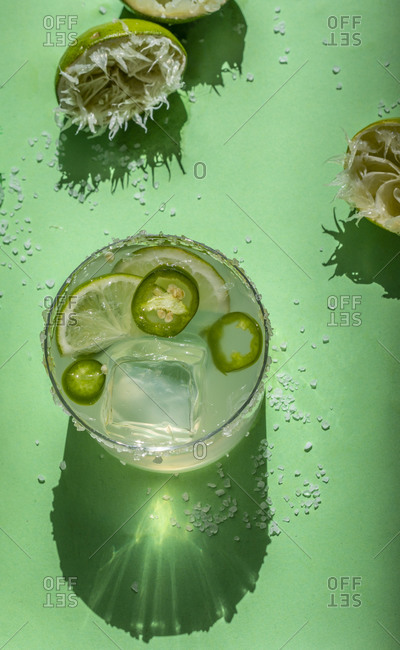 Margarita with lime and jalapeno on a green background
