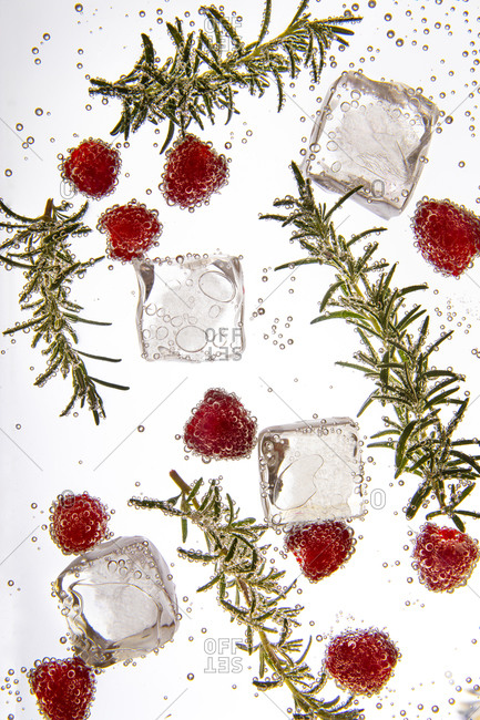 Close up of a cocktail with rosemary and raspberries