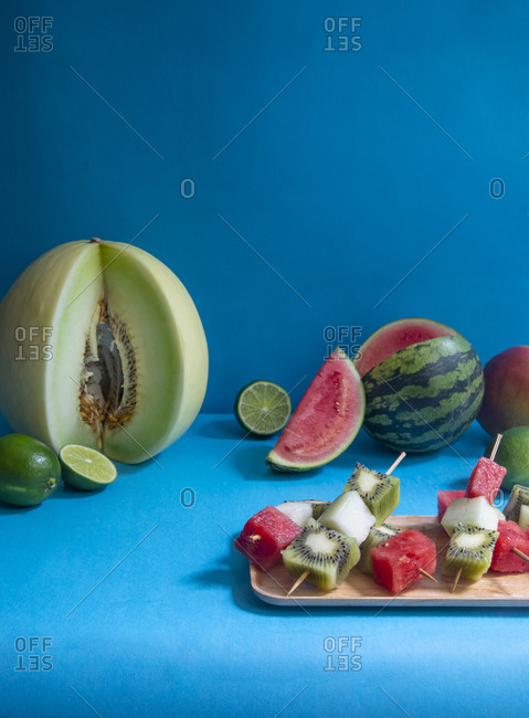 Fruit skewers being prepared on a blue background