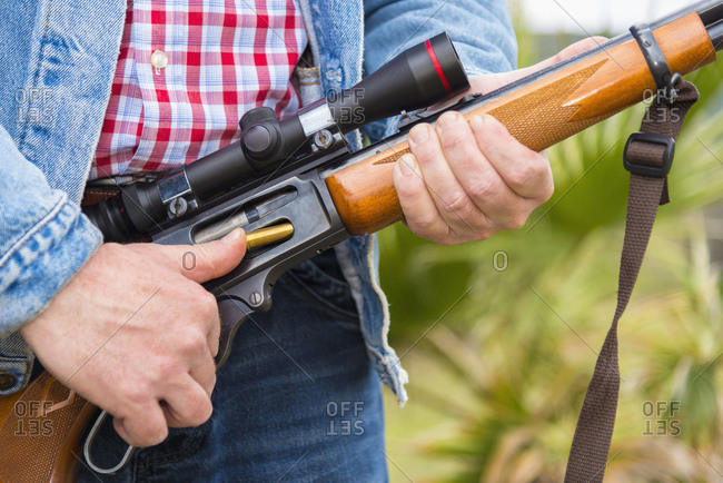 Texas- Cowboy loading ammunition in hunting rifle- close up