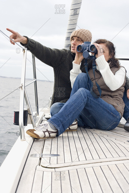 Germany- Baltic Sea- Lubecker Bucht- Young couple on boat- woman looking through binoculars