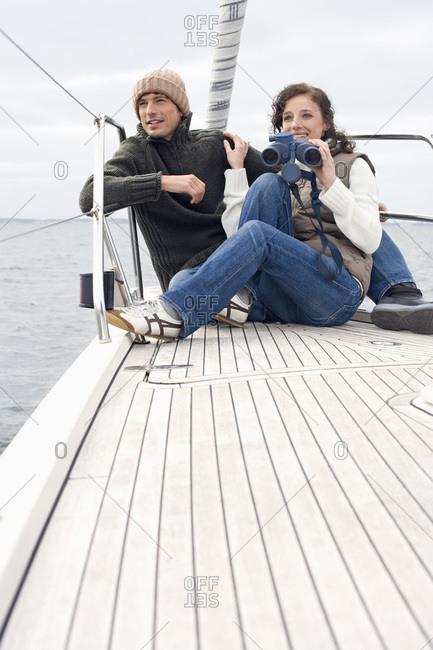 Germany- Baltic Sea- Lubecker Bucht- Young couple on boat- woman holding binoculars