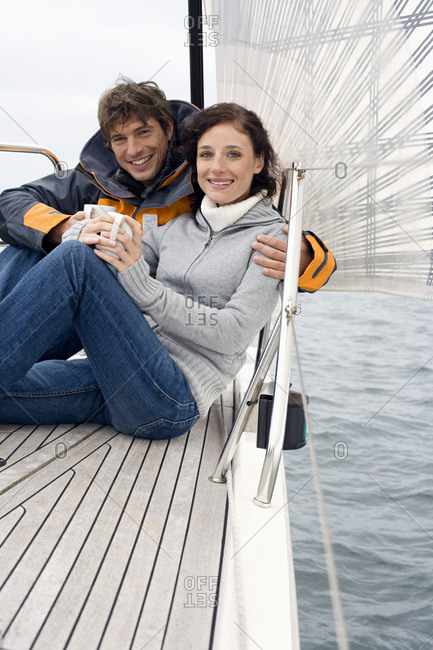 Germany- Baltic Sea- Lubecker Bucht- Young couple on sailing boat sitting and holding mugs