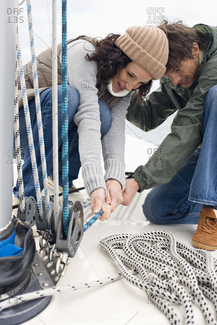 Germany- Baltic Sea- Lubecker Bucht- Young couple on sailing boat pulling rope- close-up