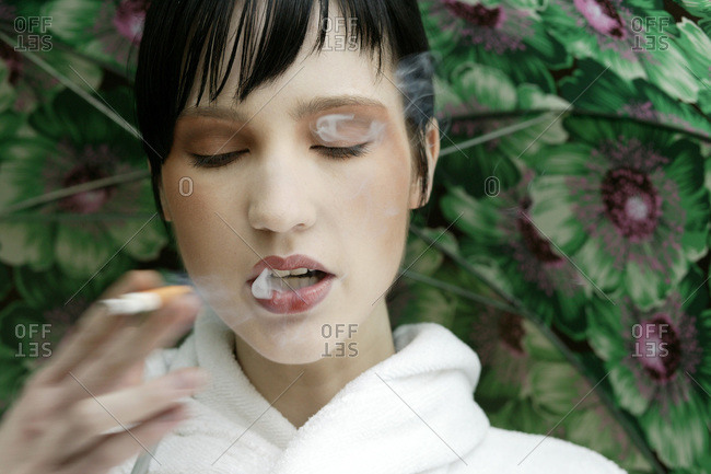 Young woman smoking against a floral background