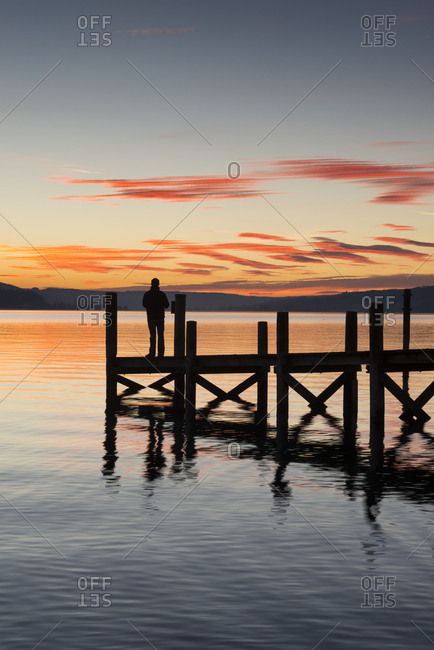 Germany- Baden Wuerttemberg- Person standing on pier at Lake Constance at dusk