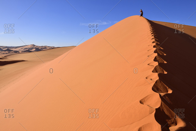 Algeria- Sahara- Tassili N'Ajjer National Park- Tadrart- woman hiking a dune of Tin Merzouga