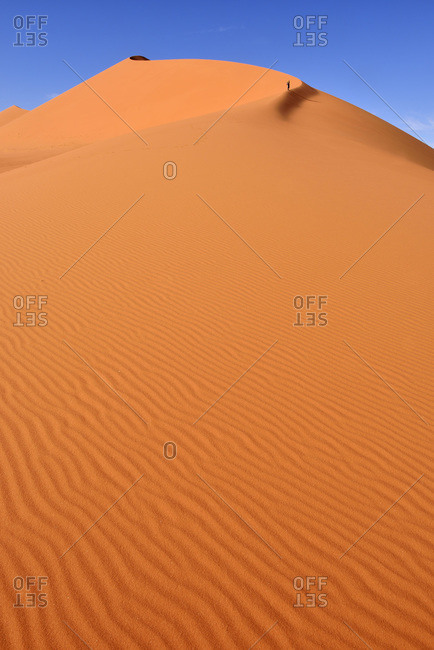 Algeria- Sahara- Tassili N'Ajjer National Park- Woman walking in the dunes of Tin Merzouga