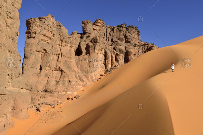 Algeria- Tassili n' Ajjer- Tadrart- Sahara- Tassili n' Ajjer National Park- woman walking on sand dune in of Moul Nag