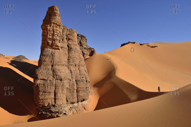 Algeria- Tassili n' Ajjer- Tadrart- Sahara- Tassili n' Ajjer National Park- view to sand dunes and rocks of Moul Nag with people at background
