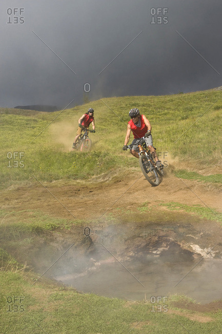 Iceland- Men mountain biking in hilly landscape