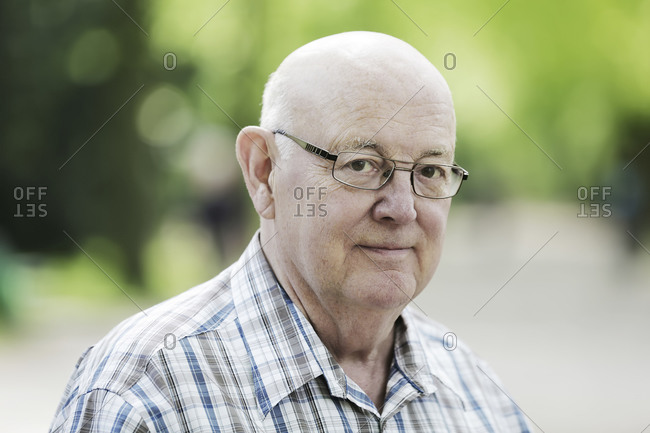 Germany- North Rhine Westphalia- Cologne- Portrait of senior man with glasses in park- smiling