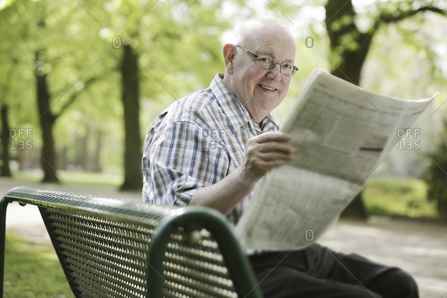 Germany- North Rhine Westphalia- Cologne- Senior man reading newspaper on bench in park